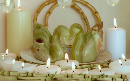 two onyx swans surrounded by candles