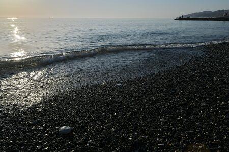 sea coast with pebble beach at sunset
