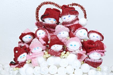 family of toy snowmen in red hats and scarves