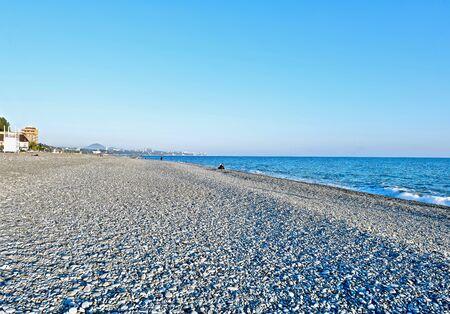 sea coast with pebble beach and city
