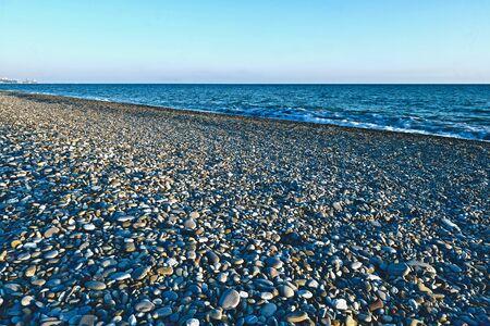 sea coast with pebble beach and city Reklamní fotografie