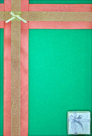 frame with yellow and red fabric ribbons and a small gift box on a green background