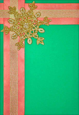 frame with yellow and red fabric ribbons and a golden snowflake on a green background Banco de Imagens