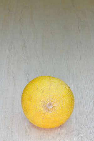 isolated orange melon in peel on wooden table Reklamní fotografie