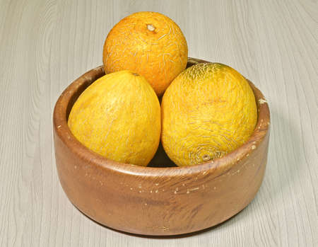 yellow-orange melons in a peel in a wooden bowl Reklamní fotografie