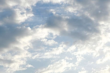 Light blue sky with light gray and white clouds in diffused light
