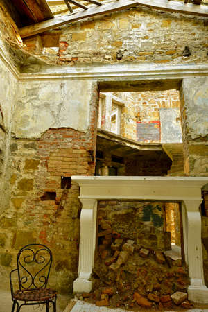 Ruins of an old building with rooms and floors and a dilapidated fireplace with a hole in the wall