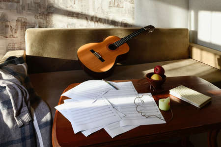 Still life in a room in the rays of the sun with a coffee table and staves located on it and a guitar lying on the sofa Standard-Bild