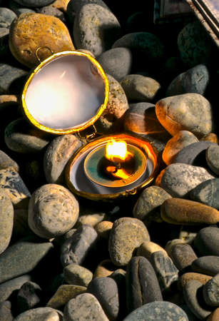 Small oval open box made of natural shell sashes with a burning candle inside on sea pebbles at dusk