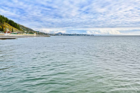 seascape with cloudy sky and mountainous city coast with cape on the horizon Standard-Bild