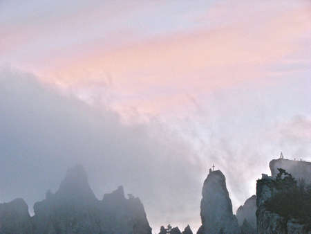 Silhouettes of the pointed tops of the rock against the background of the cloudy sky in the fog at sunset
