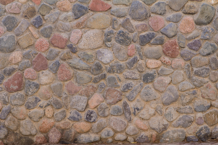 Ancient stone wall of round stones with gray cement