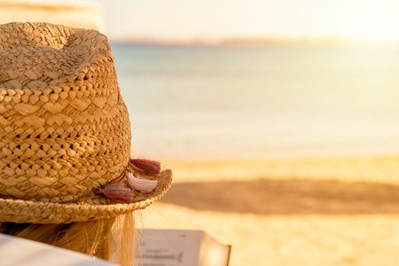 girl in a straw hat reading a book on the beach of the red sea as a symbol of relaxation