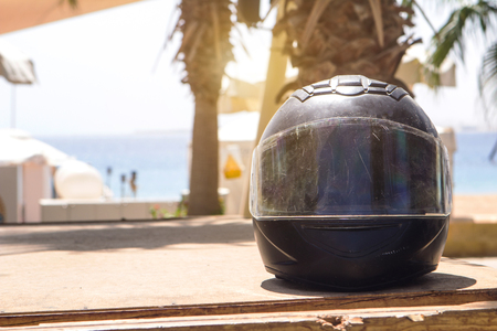 shabby black motorcycle helmet rider in scratches on the background of the red sea and palm trees under the sun place for text Stock Photo