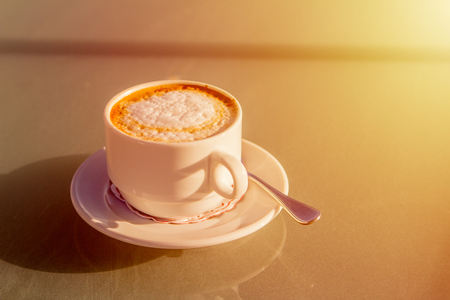 cup of cappuccino on a street table before orange sunset