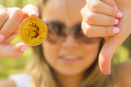 unhappy woman holding a golden bitcoin and showing thumbs down
