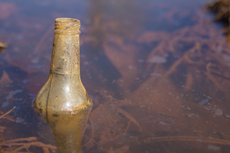 Garbage bottle floating in the water with other trash and garbage piled up along the flooded 스톡 콘텐츠