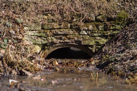 Water flowing under a old stone bridge.
