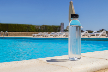 a bottle of pure water against a pool background as a symbol of a lack of water in the body in the summer in the sun Stock Photo