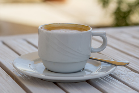 white cappuccino cup on a white wooden table on a sunny summer day Stock Photo