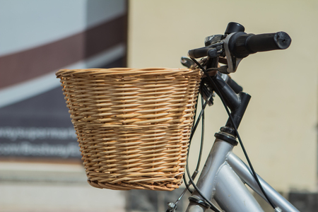 Bicycle with wicker basket on light background