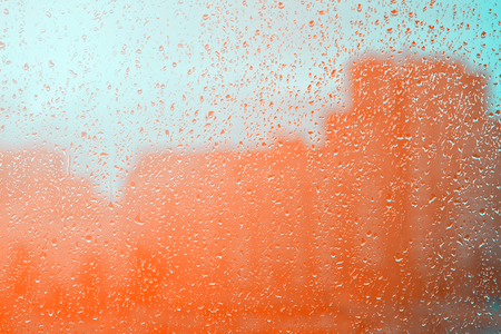 Natural water drops background on glass. Blurred city orange tone. Stock Photo
