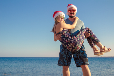 man carrying woman in christmas hats and sunglasses at the beach of the sea.