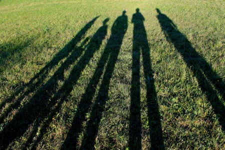 long shadows of family created by sunset in nature Banque d'images