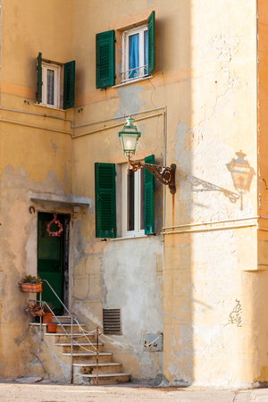 lamp post: Shutters and door on ancient mediterranean facade with a lamp post
