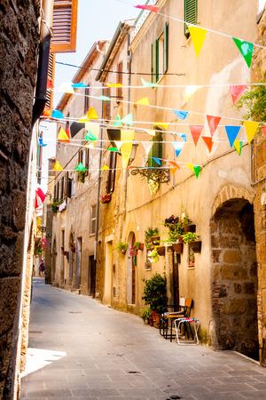 Bunte Party-Fahnen wehen in einer kleinen Gasse während eines Dorffest in Pitigliano, Italien Standard-Bild