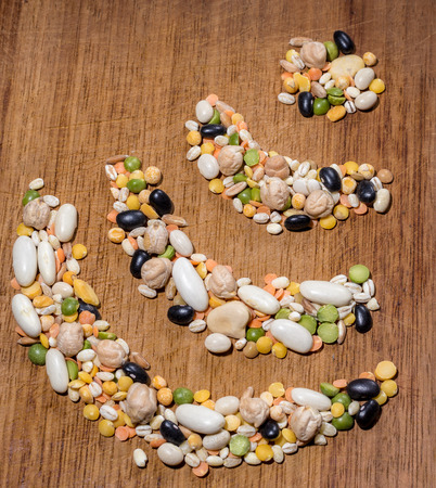 frugal: wifi shaped handful of legumes on a wooden chopping board