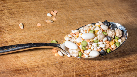 frugal: every sort of legumes inside a spoon on a wooden chopping board