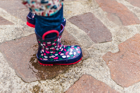 wellies: Child wearing rain boots jumping into a puddle Stock Photo