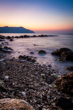 long exposure at Sunset on a beach stones - Conero, Italy