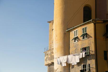 Laundry drying at the sun from house near Basilica Santa Maria Assunta in Camogli. Genoa, Ligury Italy