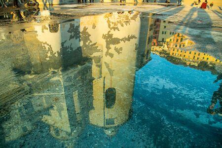 Basilica Santa Maria Assunta reflected on a sea water puddle in Camogli. Ligury, Genoa, Italy