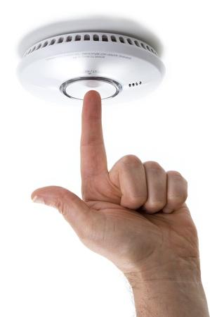 Hand mit ausgestrecktem Zeigefinger Testen einer inländischen Feuer- Rauchmelder Detektor auf einem weißen Hintergrund