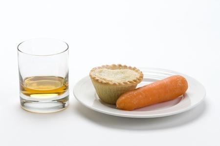 carne picada: ofrece comida tradicional de pastel de carne picada, el whisky y una zanahoria a la izquierda en Navidad para Papá Noel y Rudolph, el reno de nariz roja Foto de archivo