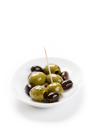 kalamata and conservolia olives in a white bowl isolated against a white background photo