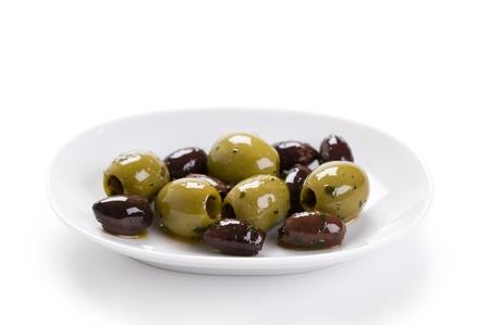 kalamata: kalamata and conservolia olives in a white bowl isolated against a white background