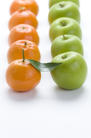 clementines: oranges and apples in rows on a white background - clementines and granny smith varieties