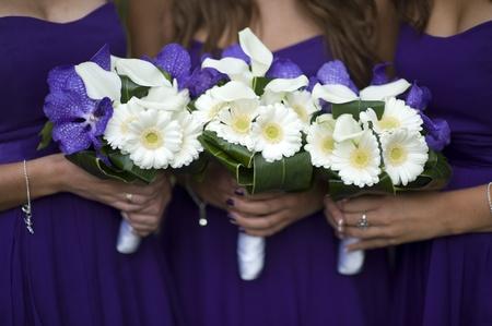 Brautjungfern halten Blumensträuße von weißen Gerbera, weißen Lilien und lila Orchideen Lizenzfreie Bilder