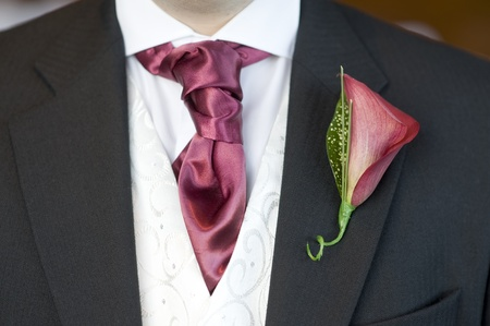 man with red cravat and lily buttonhole flower