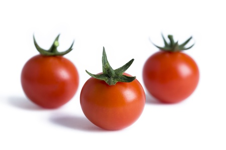 three ripe cherry tomatoes isolated on a white background photo
