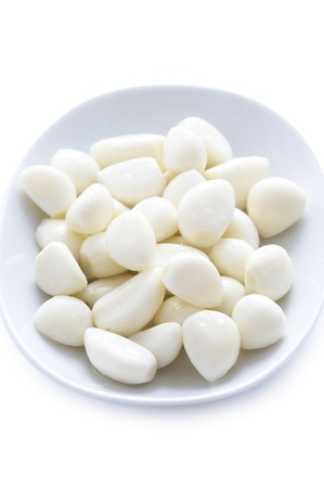 peeled pickled garlic cloves in a dish on a white background