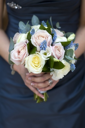 blue rose: woman in a blue dress holding a bouquet of spring flowers including roses, muscari and ranunculus