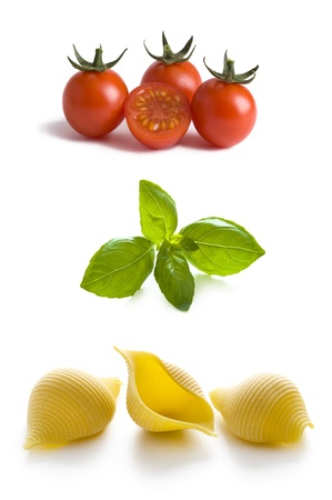 frutas secas: conchas conchiglioni pastas, tomates y hojas de albahaca aislados