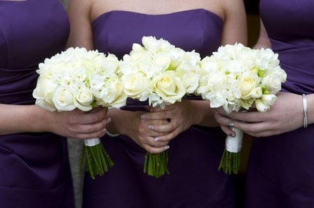 three bridesmaids holding wedding bouquets of roses