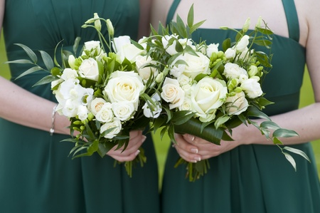 bridesmaids in green dresses holding bouquet of roses at a wedding Stock Photo - 13440861