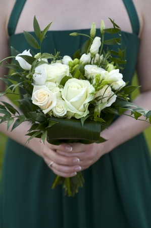 bridesmaids: bridesmaids in green dresses holding bouquet of roses at a wedding Stock Photo
